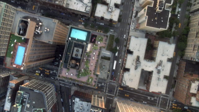 aerial birdseye pov of high rise apartment buildings roofs in greenwich village. some buildings have swimming pools on roof.  see washington square park below where fifth avenue terminates. - greenwich village stock videos & royalty-free footage