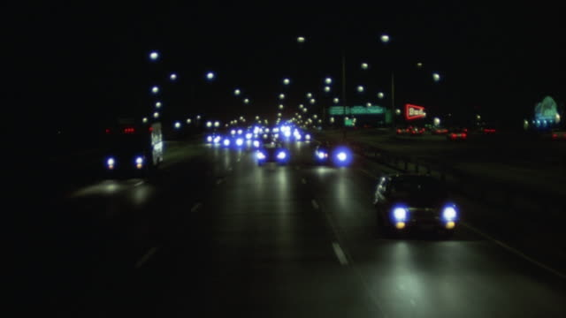 PROCESS PLATE STRAIGHT BACK OF 1980'S CARS DRIVING ON FREEWAY OR HIGHWAY. POV HIGH ANGLE DOWN OF FRONT OF CARS FROM BACK OF MOVING VEHICLE. MANY CARS ON FREEWAY. TRAFFIC FLOWS STEADILY. HEADLIGHTS OF CARS HAVE BLUE OR PURPLE TINT.