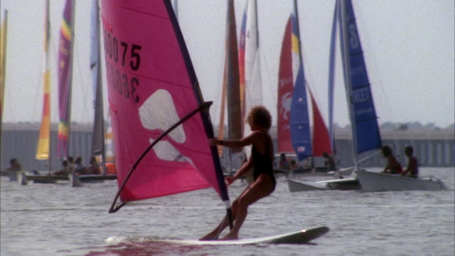 MEDIUM ANGLE OF DOZENS OF CATAMARANS SAIL IN OCEAN. MOST LIKELY DURING RACE. SEE ROAD IN FAR BACKGROUND. WOMAN WINDSURFING IN FOREGROUND.