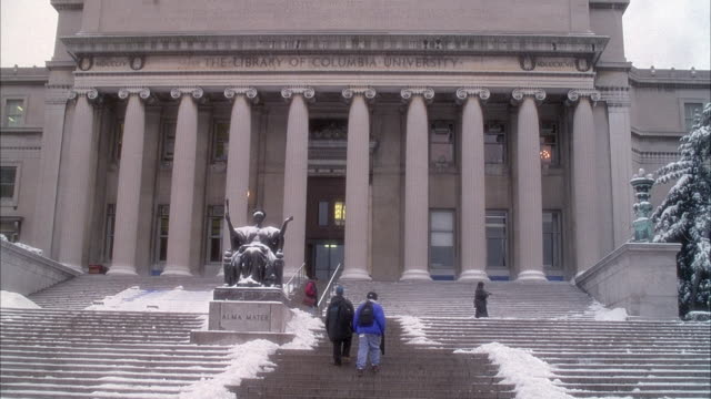 MEDIUM ANGLE OF ENTRANCE TO BUTLER LIBRARY AT COLUMBIA UNIVERSITY. ENGRAVED SIGN OVER IONIC COLUMNS READS THE LIBRARY OF COLUMBIA UNIVERSITY. STUDENTS WALK UP STEPS, SNOW ON GROUND, WINTER.