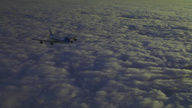 MEDIUM ANGLE AIR FORCE ONE FLYING ACROSS OF CLOUDS AT DUSK TOWARD FRONT RIGHT.