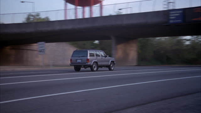 medium angle of freeway in foreground with minimal traffic. pans right as gray jeep cherokee appears from left and travels on freeway to right. see overpass with lit sign reading seattle-tacoma international airport. - vierradantrieb stock-videos und b-roll-filmmaterial