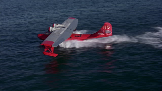 aerial of small dual propeller red airplane landing in ocean water or sea. see water splash underneath water plane as plane slowly comes to a stop and turns engine off. seaplanes. - splashdown stock videos & royalty-free footage