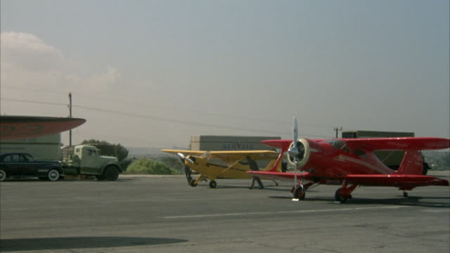 PAN  RIGHT TO LEFT OF SMALL AIRFIELD. PANS LEFT FROM RED BIPLANE AND YELLOW PROPELLER AIRPLANE TO RED PROPELLER PLANE WITH PROPELLER SPINNING.