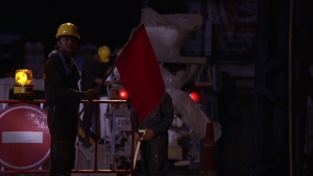 medium angle of construction site with concrete mixer, barrier with signs and warning lights. worker man with banner retreats as he waves away approaching person who is offscreen. - baustelle stock-videos und b-roll-filmmaterial