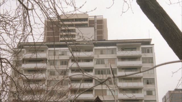 medium angle of ten story white apartment building with balconies extending out from structure. see taller building in background above apartments. - brick house stock videos & royalty-free footage