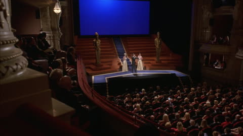 high angle down of audience sitting in theater for awards ceremony or show. see two golden oscars on each side of stage and two women dressed in gold ball gowns standing on stage. audience applauds. pov from box seat. - award stock videos & royalty-free footage