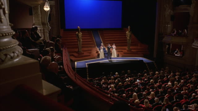 high angle down of audience sitting in theater for awards ceremony or show. see two golden oscars on each side of stage and two women dressed in gold ball gowns standing on stage. audience applauds. pov from box seat. - auszeichnung stock-videos und b-roll-filmmaterial