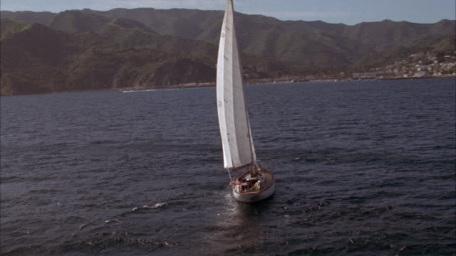 MEDIUM ANGLE OF SAILBOAT ON OCEAN HEADING RIGHT. CAMERA PANS RIGHT AND PULLS BACK, SEE CATALINA ISLAND SHORE WITH MOUNTAINS IN BACKGROUND.