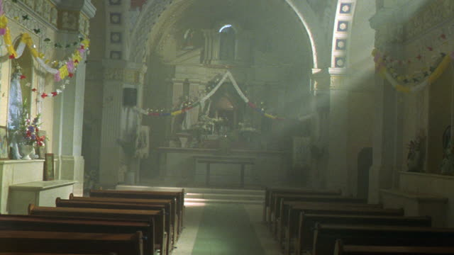 stockvideo's en b-roll-footage met medium angle of catholic church interior. see empty pew rows with light shining down from high windows. camera moves through church and pans around to walls. see paintings of jesus christ. pan to memorial or shrine area with flowers and paintings. - katholicisme
