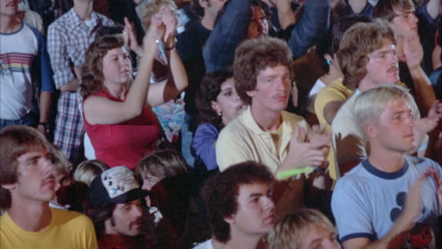 CLOSE UP. YOUNG ROCK CONCERT AUDIENCE IN EARLY 1980'S ATTIRE. CROWD STANDS WITH ARMS RAISED, CLAPPING AND PUMPING THE AIR. SOME DANCE. PAN OVER CROWD, STOP ON SEVERAL GROUPS OF PEOPLE WATCHING CONCERT. CONCERT LIGHT SHOW FALLS ON AUDIENCE.