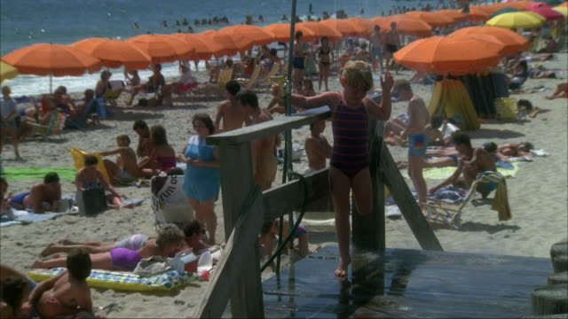 medium angle of girl in shower station washing off at beach. rows of orange parasols, crowd in bathing suits and coast in left background. - kinder beim duschen stock-videos und b-roll-filmmaterial