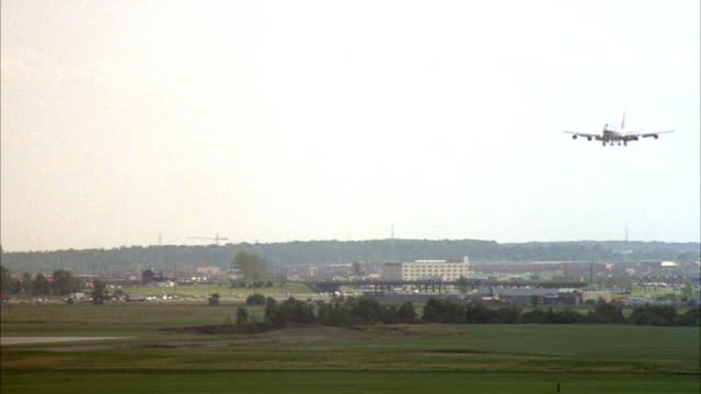 tracking shot of commercial airliner landing on runway at airport, two other planes in foreground. - luftfahrzeug stock-videos und b-roll-filmmaterial