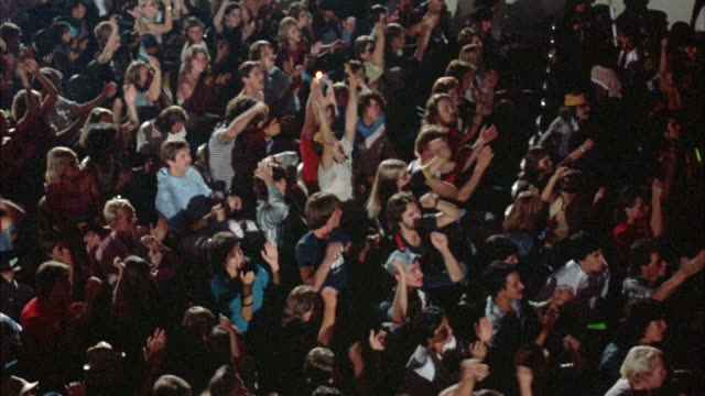 CLIP IS A HIGH ANGLE DOWN SHOT OF A ROCK CONCERT AUDIENCE (MADE UP OF MOSTLY YOUNG ADULTS DRESSED IN EARLY 1980'S ATTIRE).  THE CROWD IS SHOWN, AT THE BEGINNING OF THE SHOT, SEATED AND CALM.