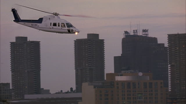 pan left to right of helicopter flying in sky, lands on landing pad on dock in middle of river. see new york city skyline in background. see soldiers walking around dock. - helicopter landing stock videos and b-roll footage