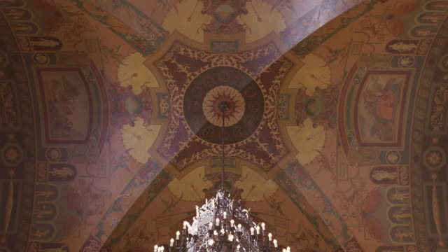 vidéos et rushes de up angle of the lobby or foyer or atrium of the millennium biltmore hotel in los angeles. camera pans down. chandeliers on ceiling. arches and columns. - cour intérieure