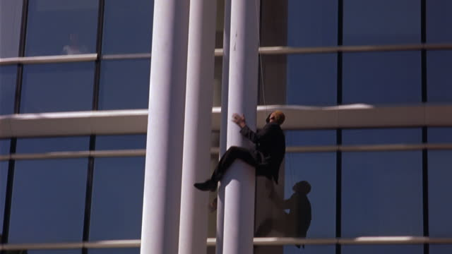 TRACKING SHOT OF MAN ATTACHED TO CABLE SLIDING DOWN WHITE STEEL SUPPORT COLUMN OF MODERN OFFICE BUILDING. TURNS UPSIDE DOWN PULLS OUT GUN AND AIMS UPWARD. TURNS RIGHT SIDE UP. GLASS WINDOWS REFLECT SURROUNDING BUILDINGS.