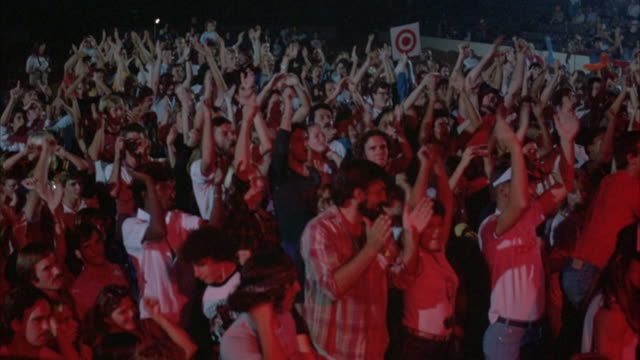 MEDIUM SHOT. ROCK CONCERT. YOUNG AUDIENCE DRESSED IN EARLY 1980'S ATTIRE. CROWD STANDS WITH ARMS RAISED, CLAPPING AND PUMPING THE AIR AS THEY DANCE TO MUSIC.