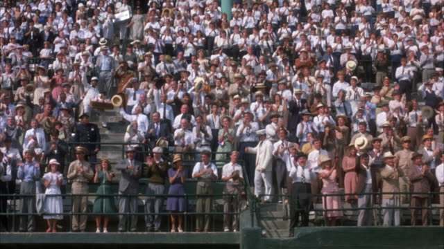 WIDE ANGLE OF SPECTATORS IN BASEBALL STADIUM BLEACHERS. PANS SLIGHTLY RIGHT TO CROWD REACTING TO SOMETHING OFF SCREEN AND STANDING AND CLAPPING.