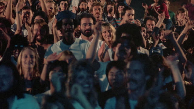 close up. young rock concert audience dressed in early 1980's attire reacts to music, clap, dance and pumping the air with arms raised. pan right, stopping often to focus on various groups of people in concert crowd. light show falls on audience. - pubblico video stock e b–roll
