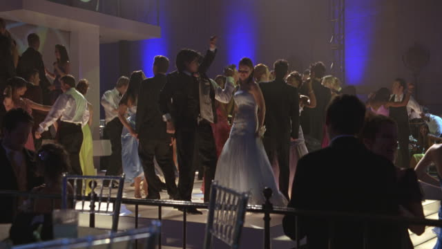 wide angle of teenagers dancing at prom or party or celebration. could be in hotel or  school gym. evening gowns and tuxedos. - 高校卒業ダンスパーティ点の映像素材/bロール