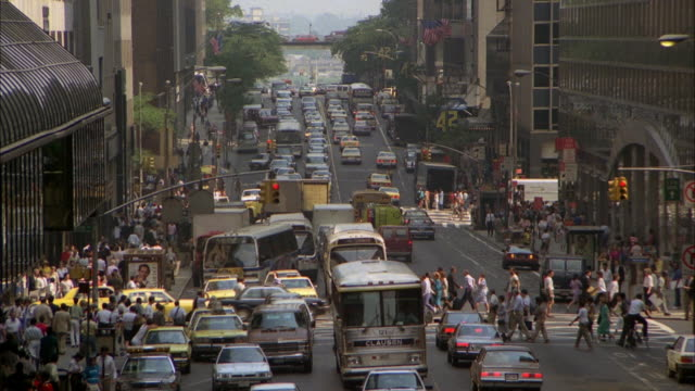 wide angle of city street in downtown new york city. heavy traffic in streets, pedestrians on sidewalks, crosswalks, and streets. - 1986 stock-videos und b-roll-filmmaterial