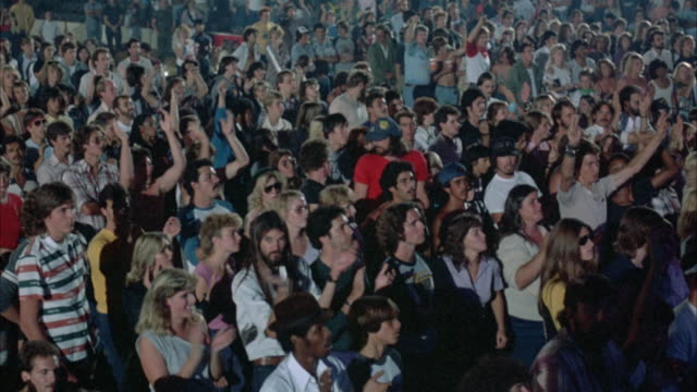 SHOT BEGINS WITH A PAN, RIGHT TO LEFT, ACROSS A ROCK CONCERT AUDIENCE (YOUNG AND DRESSED IN EARLY 1980'S ATTIRE). THE CROWD IS SEEN DANCING WITH ARMS RAISED, CLAPPING AND PUMPING UP IN THE AIR,