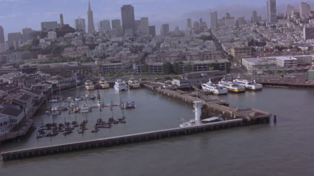 aerial. passing over san francisco bay. see piers with boats docked. shot passes from right to left, see san francisco skyline. clear day. follows around piers, passes by bay bridge. - 1989 stock videos and b-roll footage