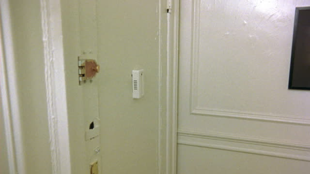MEDIUM ANGLE INTERIOR VIEW OF CLOSED WHITE FRONT DOOR TO APARTMENT OR HOME. SEE BRASS DEADBOLT LOCK ON DOOR. SEE WHITE RAISED PEEPHOLE BOX ON DOOR.
