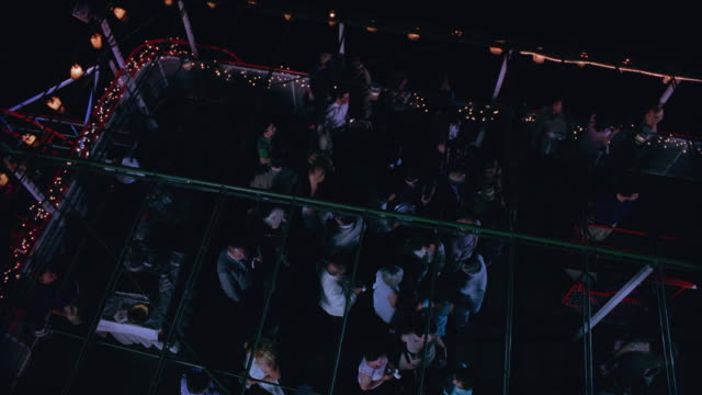 high angle down of a crowd at a party on a boat or cruise ship.  the crowd panics and waves their hands in front of their faces.  supposed to be a bat attack, could be bugs or other pest infestation or emergency. evacuation. - infestation stock-videos und b-roll-filmmaterial