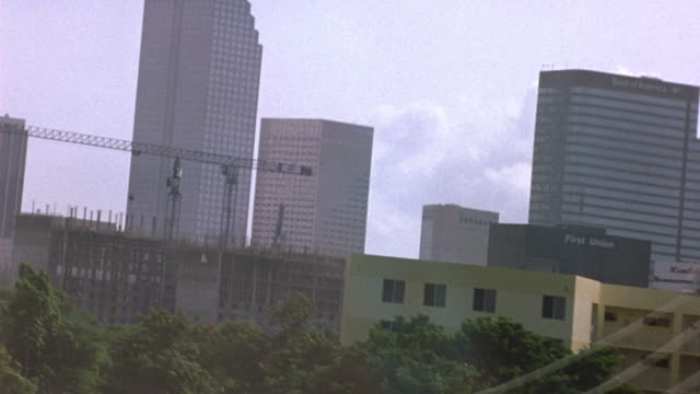 vídeos de stock, filmes e b-roll de driving pov on highway. pans right to downtown miami skyline. pans to forward pov of signs biscayne blvd downtown. see construction crane. - bulevar