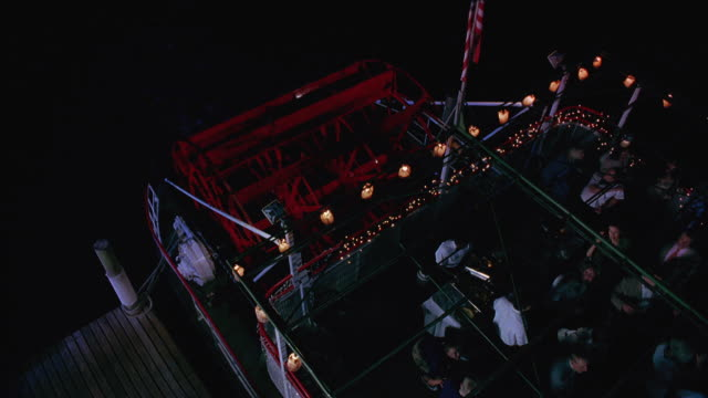 high angle down of a crowd at a party on a boat, paddleboat or cruise ship.  dark shadows flicker overhead. the crowd panics and waves their hands in front of their faces. - infestation stock-videos und b-roll-filmmaterial