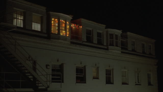 medium angle of upper floor of early 1900s apartment building.  see yellow, blue, red, pink, orange christmas lights in one window. building is white and three stories or taller. see fire escape on left. red can thrown from lighted window falls. - 非常階段点の映像素材/bロール