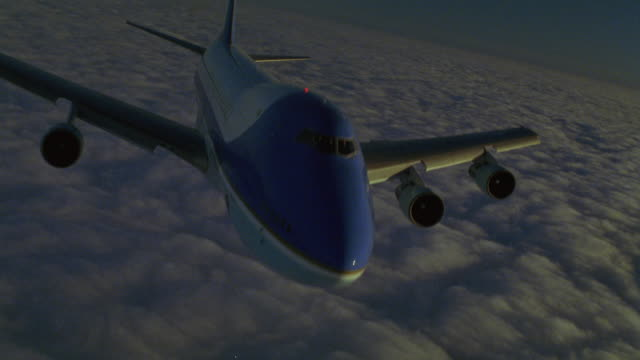 CLOSE ANGLE OF FRONT OF AIR FORCE ONE FLYING ACROSS OF CLOUDS AT DUSK TOWARD FRONT RIGHT. AIRPLANE DESCENDS AS CAMERA PANS UP TO HORIZON IN BACKGROUND.