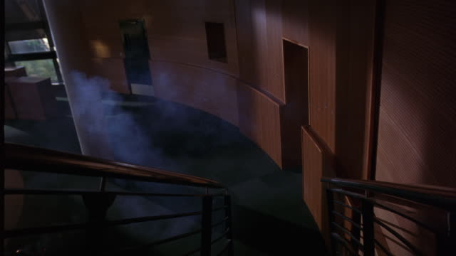 vidéos et rushes de high angle down of stairs leading into lobby of upper-class building. smoke and sparks from beneath staircase. carpet and wood panel walls. could be office building. - hall d'accueil