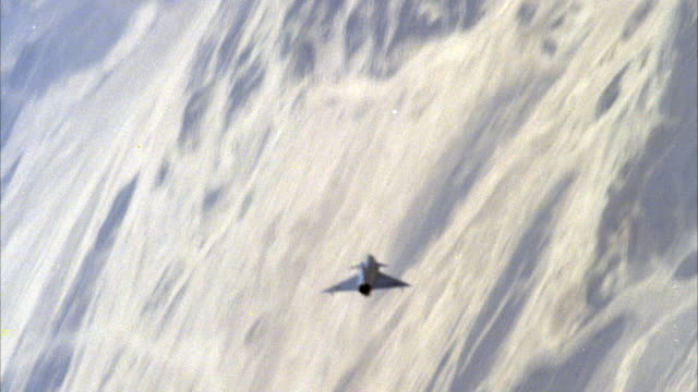tracking shot of a camouflage f-16 fighter jet flying. pov is of top of jet. cuts to two other f-16 fighter jets. see land below. neg cut. - jagdflugzeug stock-videos und b-roll-filmmaterial