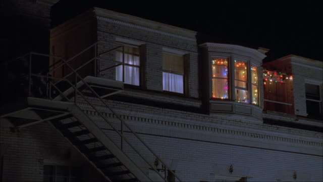 MEDIUM ANGLE OF TOP LEVEL OF APARTMENT BUILDING. SEE FLASHING CHRISTMAS LIGHTS IN ONE WINDOW. STAIRCASE ON LEFT LEADS UP TO TOP FLOOR.
