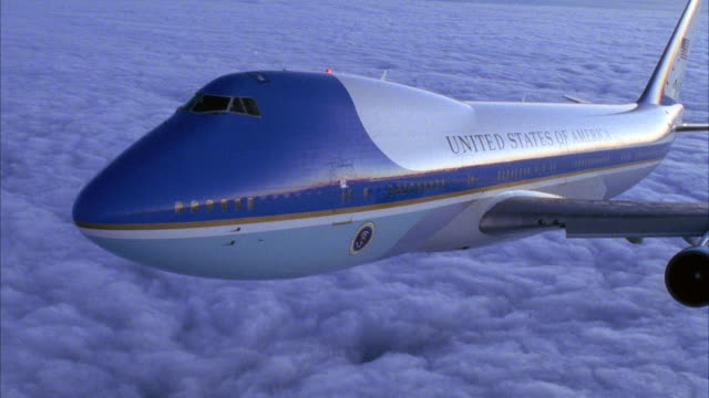 CLOSE ANGLE OF FRONT COCKPIT OF AIR FORCE ONE FLYING LEFT ABOVE LAYER OF CLOUDS ON BOTTOM.