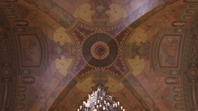 UP ANGLE OF THE LOBBY OR FOYER OR ATRIUM OF THE MILLENNIUM BILTMORE HOTEL IN LOS ANGELES. CAMERA PANS DOWN. CHANDELIERS ON CEILING. ARCHES AND COLUMNS.