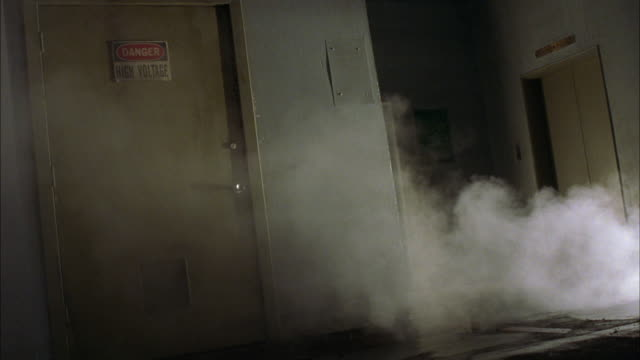 CANTED MEDIUM ANGLE OF DOORS WITHIN BUILDING, POSSIBLY OFFICE BUILDING OR PARKING GARAGE. SEE TAN OR GREEN DOOR FRAME LEFT, WITH SIGN READING DANGER HIGH VOLTAGE. SEE ELEVATOR FRAME RIGHT. SEE SMOKE CONTINUALLY POURING INTO HALLWAY FROM FRAME RIGHT.