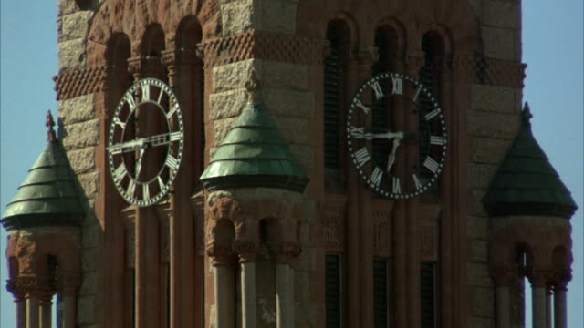 wide angle of clock portion only of victorian era clock tower, ellis county courthouse. brick and sandstone building. clock reads 6:45. could be college, university, government building or church, cathedral. blue sky. - turmuhr stock-videos und b-roll-filmmaterial