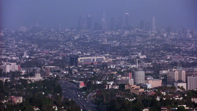 wide angle of city with highway in foreground and downtown city skyline in background.  multi-story buildings. capitol records building and hollywood neighborhood visible on right. smog. office buildings. - city of los angeles stock videos & royalty-free footage