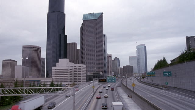 vidéos et rushes de wide angle of eight-lane freeway, highway through downtown seattle.  skyscrapers, office buildings. cloudy day. - seattle