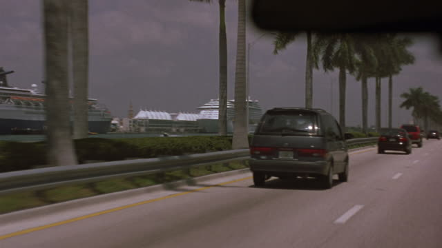 vídeos de stock, filmes e b-roll de medium angle driving pov on highway next to harbor. shot pans right to left to cruise ships docked in harbor. see palm trees lined up on side of highway. - flórida eua