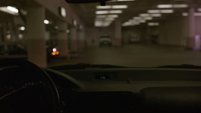 MEDIUM ANGLE PARKING GARAGE, DRIVING POV. POV TURNS RIGHT, FOLLOWING JAGUAR XJ6 CAR TO PARKING GATE. DRIVER GIVES TICKET TO ATTENDANT, SEE GATE LIFT, JAGUAR MOVES THROUGH. SEE EXIT AND ENTRANCE AREA TO LEFT. POV MOVES FORWARD TOWARDS GATE.