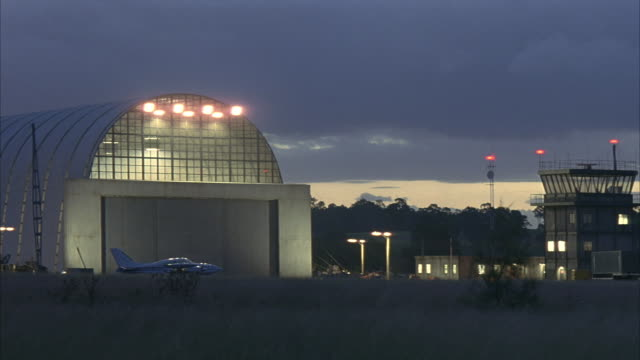 wide angle of hangar at night in small airport. airplane in front of hangar. control tower on right of screen. field in foreground. dark gray clouds. - airplane hangar stock videos and b-roll footage