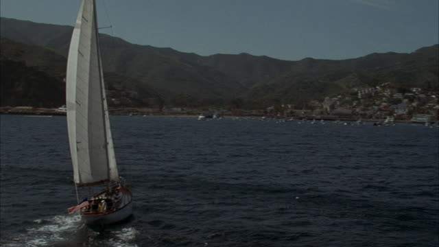 MEDIUM ANGLE OF SAILBOAT ON OCEAN HEADING RIGHT. CAMERA PANS RIGHT, SEE CATALINA ISLAND SHORE WITH MOUNTAINS IN BACKGROUND.
