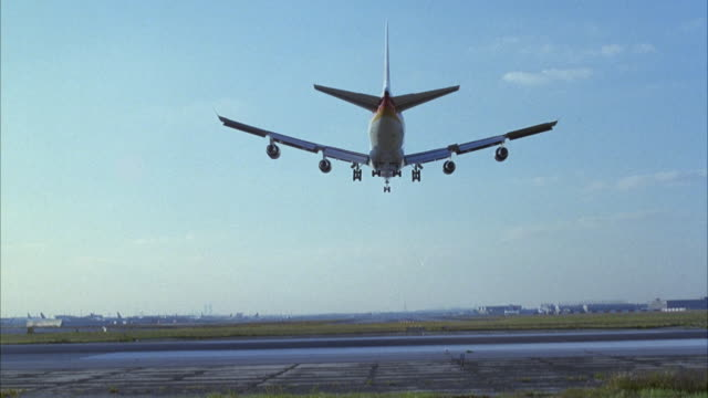 vidéos et rushes de tracking shot of commercial airliner landing at airport on runway. airplane flies overhead and lands. could be any airport. - avion