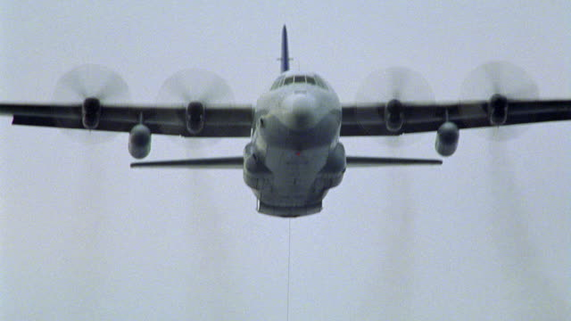 tracking shot of c-130 hercules cargo plane or refueling plane. plane has four propeller engines. see refueling hose hanging from out the back. camera pans down to show hose. propeller plane. - refuelling stock videos & royalty-free footage