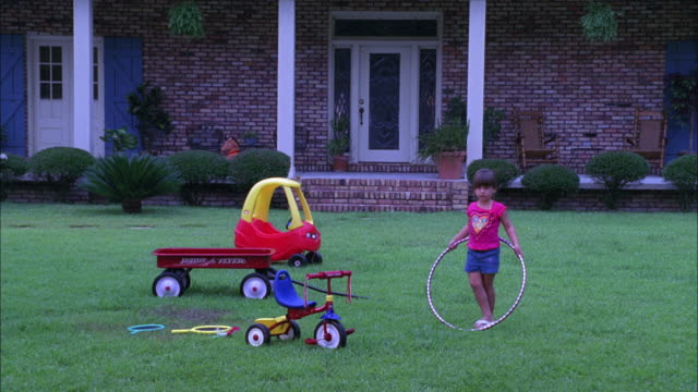wide angle of girl playing with hula hoop, wagon, and toys in front yard or lawn. middle class house or home in background. - middle class stock videos & royalty-free footage